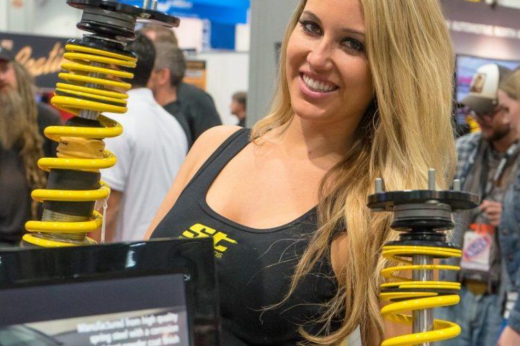 Glanz am Stand von KW automotive: Eine hübsche Dame präsentiert mit einem Lächeln die Fahrwerkskomponenten für die SEMA Las Vegas 2014-Besucher