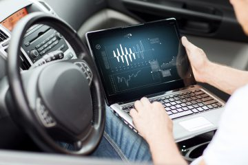 Mann sitzt mit Computer auf dem Fahrersitz, Chiptuning mit On Board Diagnose