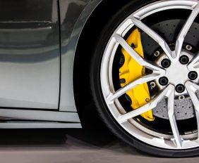 Nahaufnahme auf ein Vorderrad mit Bremsanlage und gelbem Bremssattel