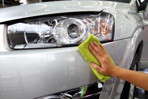 Autopolitur eines grauen Autos mit grünem Mikrofasertuch